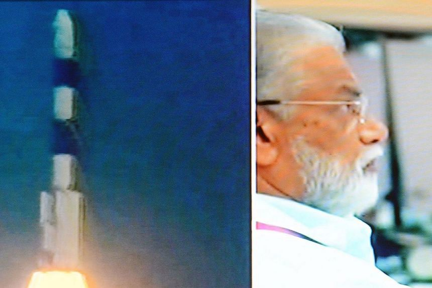 This television frame grab taken from Indian television channel NDTV, broadcasting live footage from state television Doordarshan, shows a split frame of the PSLV-C25 launch vehicle (left) carrying the Mars Orbiter probe as its payload moments after