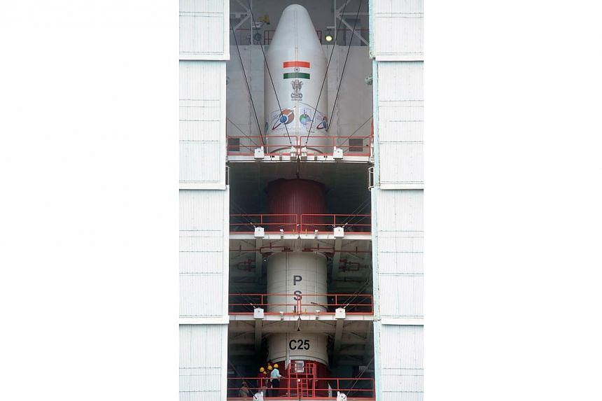 This photograph taken on Oct 30, 2013, shows Indian personnel (bottom) at the launch pad of the PSLV-C25 launch vehicle, carrying the Mars Orbiter probe as its payload, at the Indian Space Research Organisation facility in Sriharikota, ahead its plan