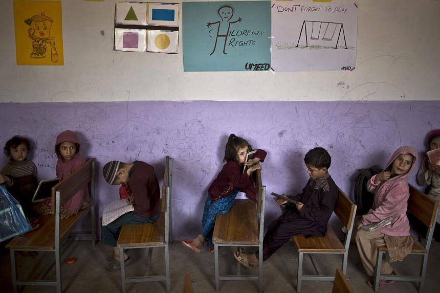 Afghan refugee schoolchildren attend class in a makeshift school on the outskirts of Islamabad, Pakistan on Tuesday, Nov 5, 2013. Pakistan hosts over 1.6 million registered Afghans, the largest and most protracted refugee population in the world, acc
