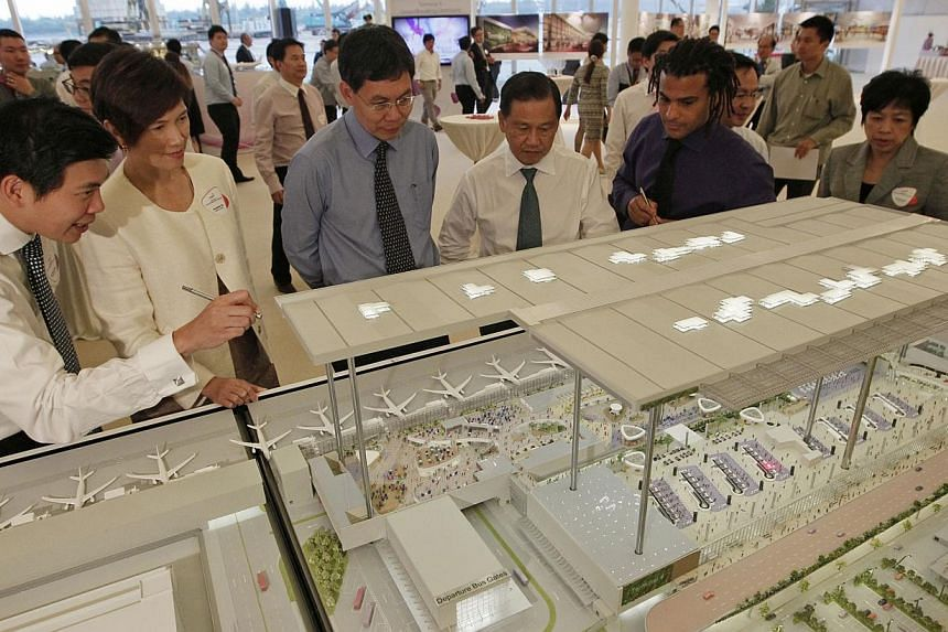 Minister for transport and guest-of-honour Lui Tuck Yew (third from left) takes a look at a model of the new Changi Airport Terminal 4 with (from left) Changi Airport Group (CAG) CEO Mr Lee Seow Hiang, Senior Minister of State (Ministry of Finance an