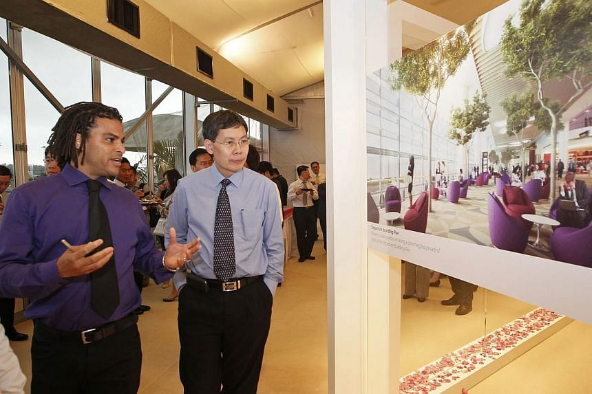 Minister for transport and guest-of-honour Lui Tuck Yew (right) takes a look at an artist's impression of a section of the new Changi Airport Terminal 4 with Benoy creative director David Buffonge after the ground-breaking ceremony held on Tuesday, N