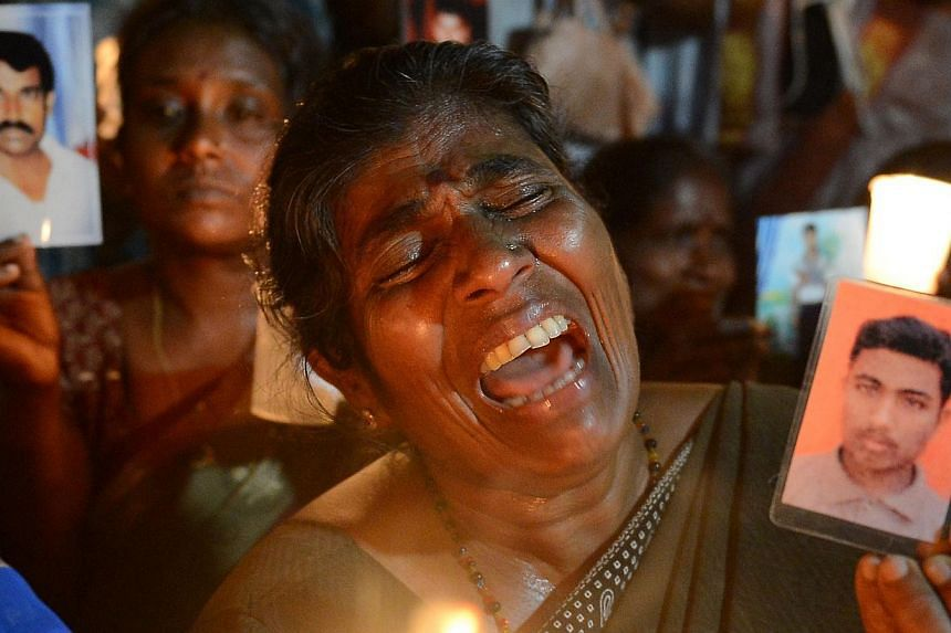 A Sri Lankan activist wails as she holds a lighted candle and a photograph during a candlelight vigil in Colombo on August 30, 2013, held to mark the International Day of the Disappeared. The vigil at Colombo's Independence Square came as UN human