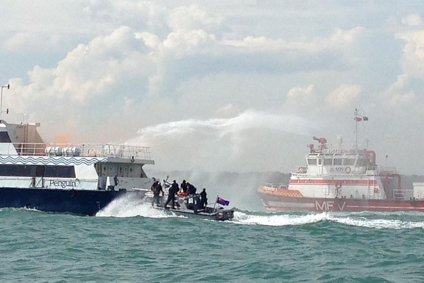 Immigration and Checkpoint Authority's Anti-Smuggling Team (speedboat in middle) storming the hijacked ferry (left), as Singapore Civil Defence Force's Marine Fire Vessel (right) puts out a fire on the ferry. This was part of a counter-terrorist sea