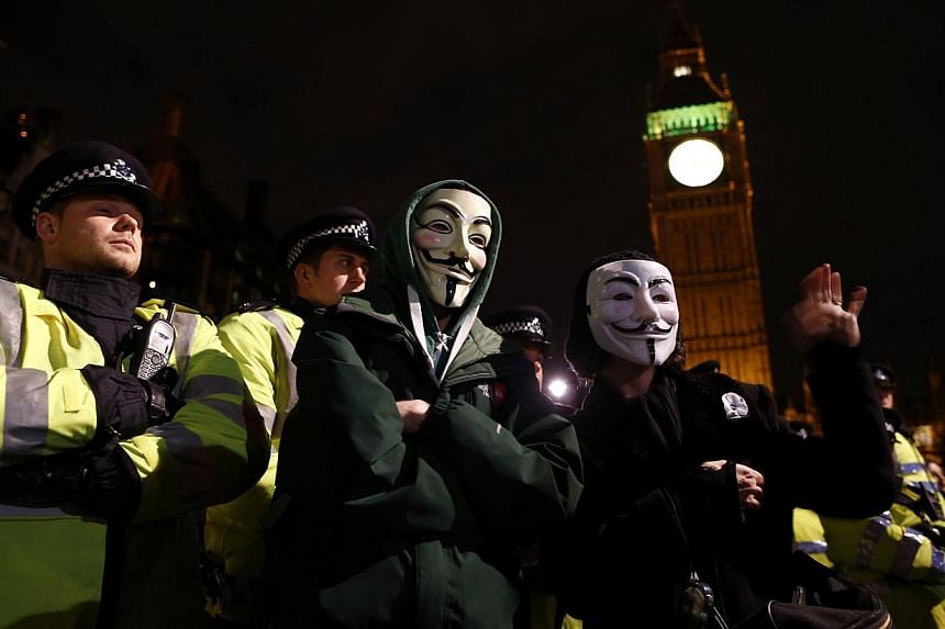 Protesters wearing Guy Fawkes masks stand in front of a line of riot police officers during a protest against budget cuts and energy prices in Westminster, central London, on Nov 5, 2013. -- PHOTO: REUTERS