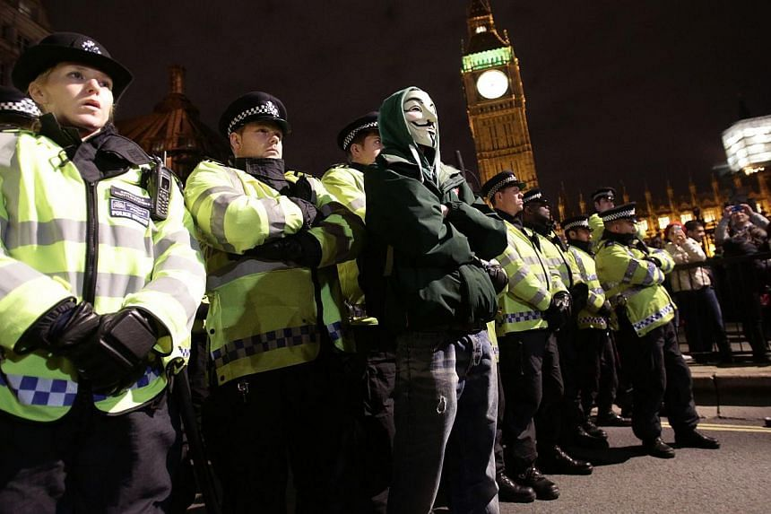 Protesters demonstrate as part of the Bonfire of Austerity protest outside the Houses of Parliament in central London on Nov 5, 2013. The demonstrators are against austerity, the bedroom tax and local cuts. -- PHOTO: AP