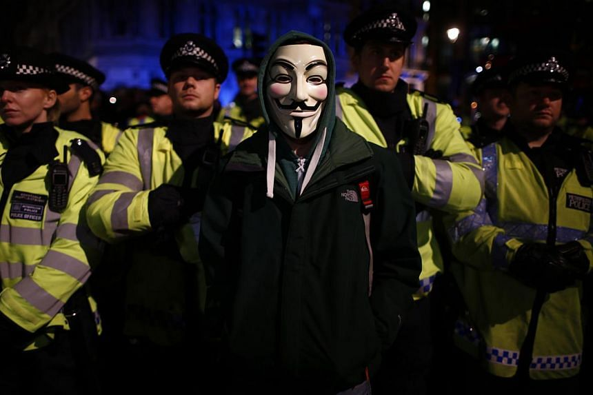 A protester wearing a Guy Fawkes mask stands in front of a line of riot police officers during a protest against budget cuts and energy prices in Westminster, central London, on Nov 5, 2013. -- PHOTO: REUTERS