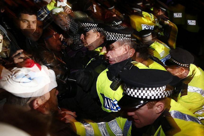 Protesters wearing Guy Fawkes masks are pushed back by riot police officers during a protest against budget cuts and energy prices in Westminster, central London, on Nov 5, 2013. -- PHOTO: REUTERS
