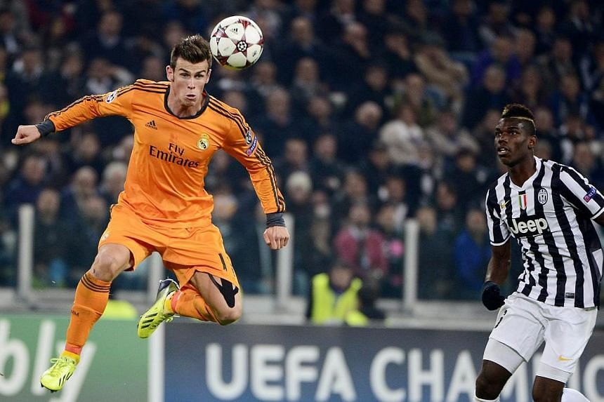 Real Madrid's Welsh striker Gareth Bale (Left) jumps for the ball next to Juventus' French midfielder Paul Pogba during the UEFA Champions League Group B football match Juventus vs Real Madrid at the Juventus stadium in Turin on Nov 5, 2013.Juv