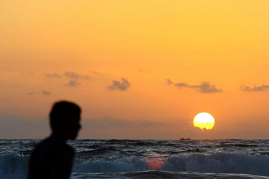 A Sri Lankan fisherman's boat sails on the horizon at sunset in Colombo on September 26, 2013. -- PHOTO: AFP