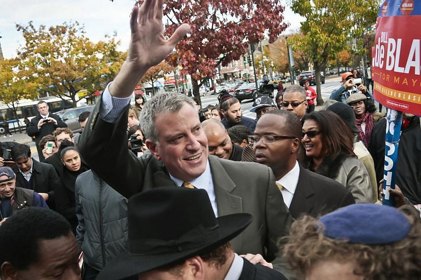 Democratic mayoral candidate Bill de Blasio waves as he arrives to meet potential voters outside the Eastern Parkway subway station in Brooklyn, New York, on Nov 5, 2013. Mr De Blasio has been elected mayor of New York, replacing billionaire Michael