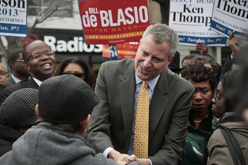 Democratic mayoral candidate Bill de Blasio, centre, accompanied by Mr Ken Thompson, fifth from right, candidate for Brooklyn district attorney, meet potential voters on Tuesday, Nov 5, 2013, in the Crown Heights section of New York's borough of Broo