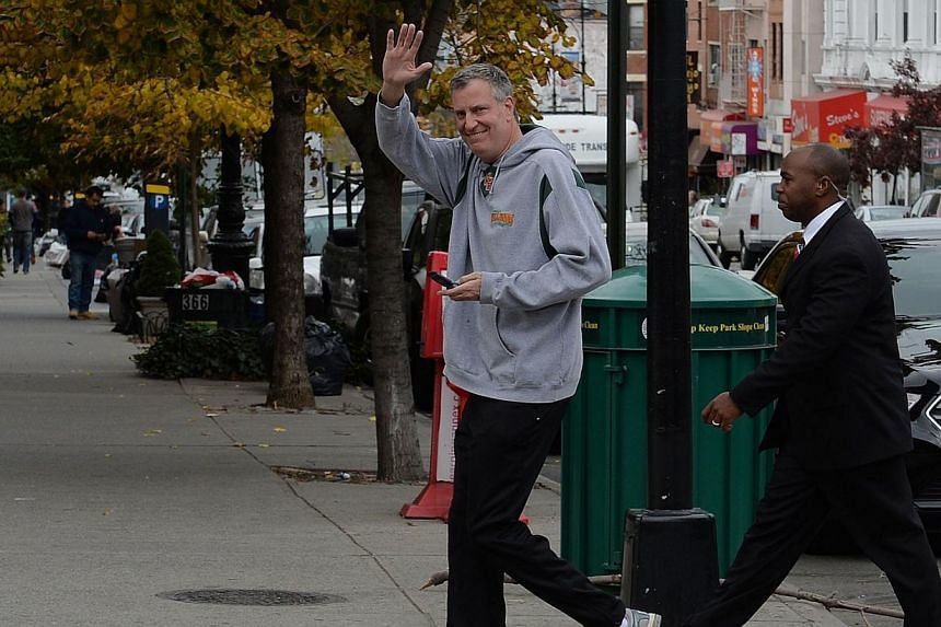 New York City Democratic mayoral candidate Bill de Blasio walks with an aide in his Park Slope neighbourhood in the Brooklyn borough of New York on Nov 5, 2013. Mr De Blasio has been elected mayor of New York, replacing billionaire Michael Bloomberg,
