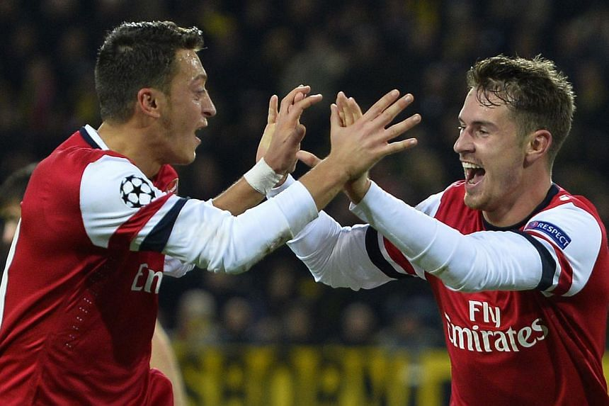 Arsenal's Welsh midfielder Aaron Ramsey (right) celebrates scoring the opening goal with Arsenal's German midfielder Mesut Ozil during the UEFA Champions League group F football match Borussia Dortmund vs Arsenal London in Dortmund, western Germany o