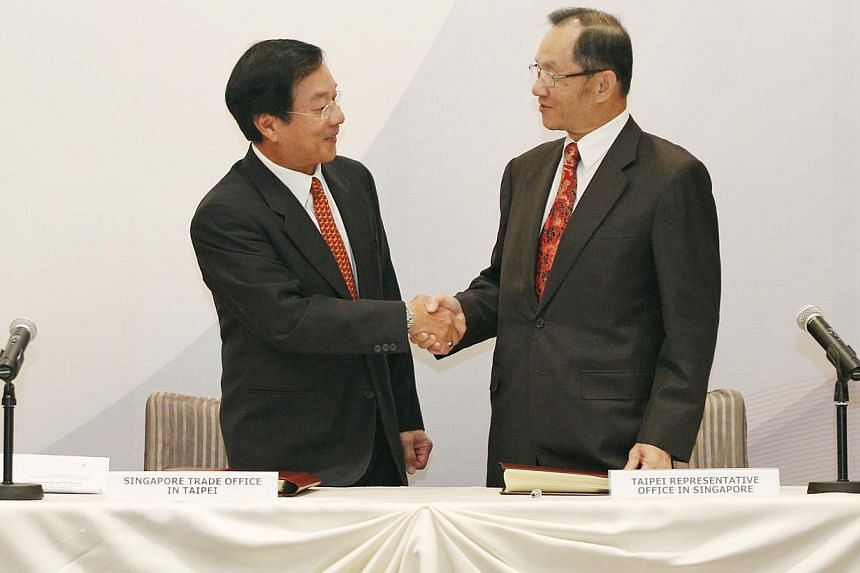 Singapore Trade Office Representative, Mr Calvin Eu Mun Hoo (left) and Representative of Taiwan Representative Office in Singapore, Mr Hsieh Fa-dah (right) exchange handshakes after the signing ceremony of an agreement between Singapore and the Separ