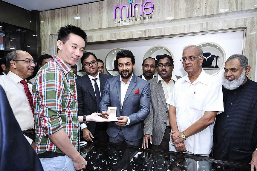 Indian actor Suriya handing over an item to a customer on the opening day of Malabar Gold & Diamonds' store in Syed Alwi Road. Malabar has its sights set on being the world's No. 1 jewellery retailer by 2015.