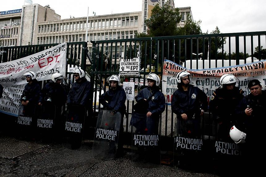 Greek riot police block the headquarters of former public broadcaster ERT in Athens on Thursday, Nov 7, 2013. Riot police stormed the former Greek state television headquarters in Athens on Thursday and evicted dozens of fired journalists,