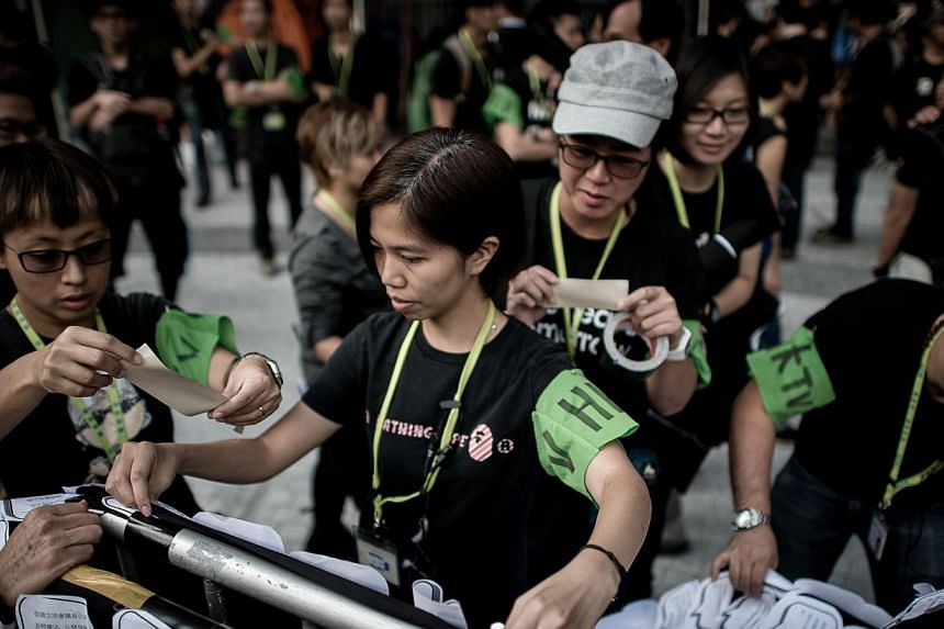 HKTV staff members hang banners displaying leaflets signed in support of the television station during a protest in front of the government building in Hong Kong on Wednesday, Nov 6, 2013. Hong Kong's decision not to grant a licence to a new TV opera