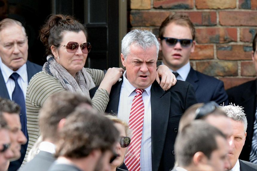 Mr Peter Lane (centre, right), father of Australian baseball player Chris Lane, who was killed in the small Oklahoma town of Duncan in the US, is surrounded by friends and family outside St Therese's Parish at Chris's funeral in Melbourne on August 2