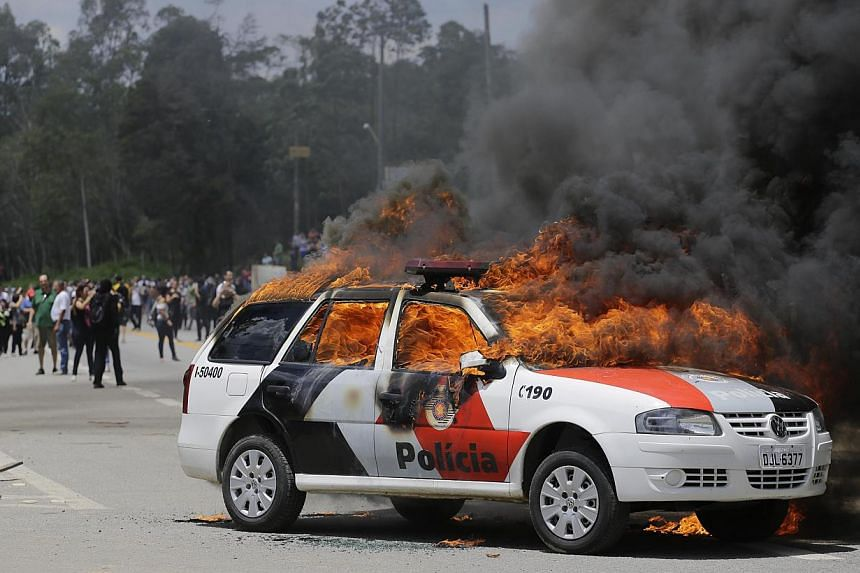 A police car burns after it was set on fire by demonstrators protesting drug testing on animals at the Instituto Royal laboratory in Sao Roque, Brazil, onSaturday, Oct 19, 2013. -- FILE PHOTO: AP