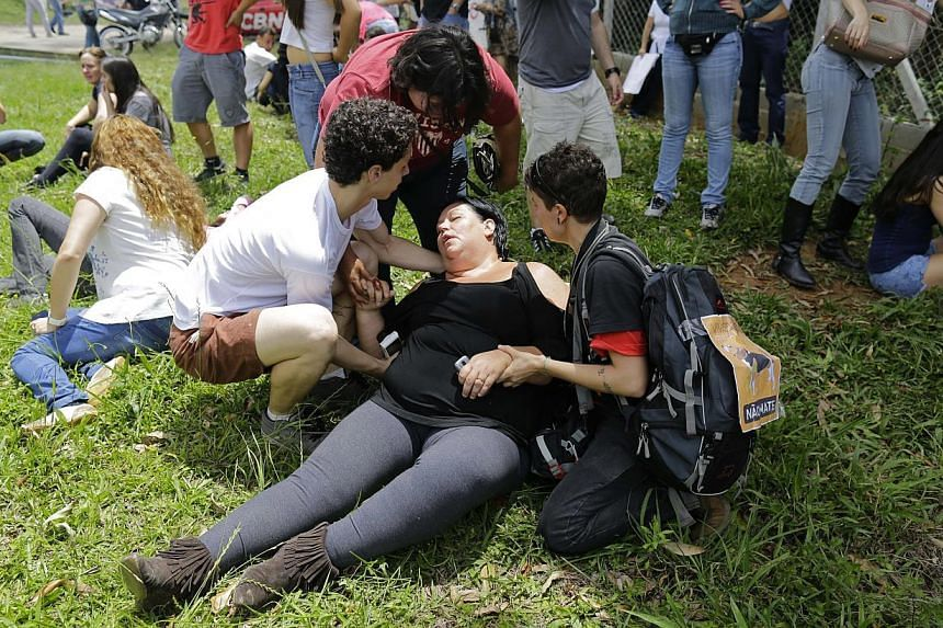 Demonstrators help a fellow protester affected by tear gas fired by police guarding the Instituto Royal laboratory during their protest against drug testing on animals in Sao Roque, Brazil, onSaturday, Oct 19, 2013. -- FILE PHOTO: AP