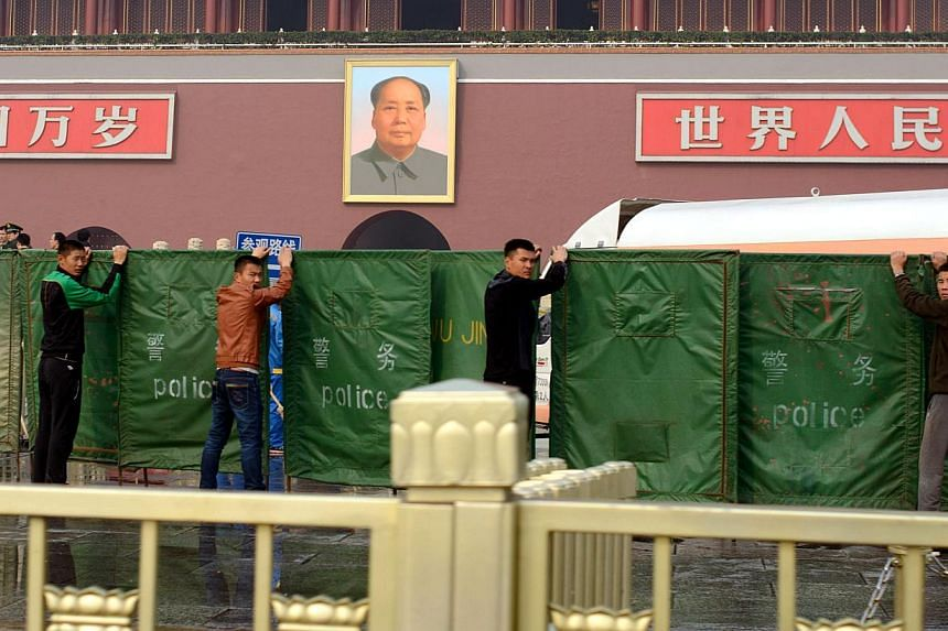 Plainclothes police hold barriers before the scene of a car crash at Tiananmen Gate in Beijing on October 28, 2013. -- PHOTO: AFP