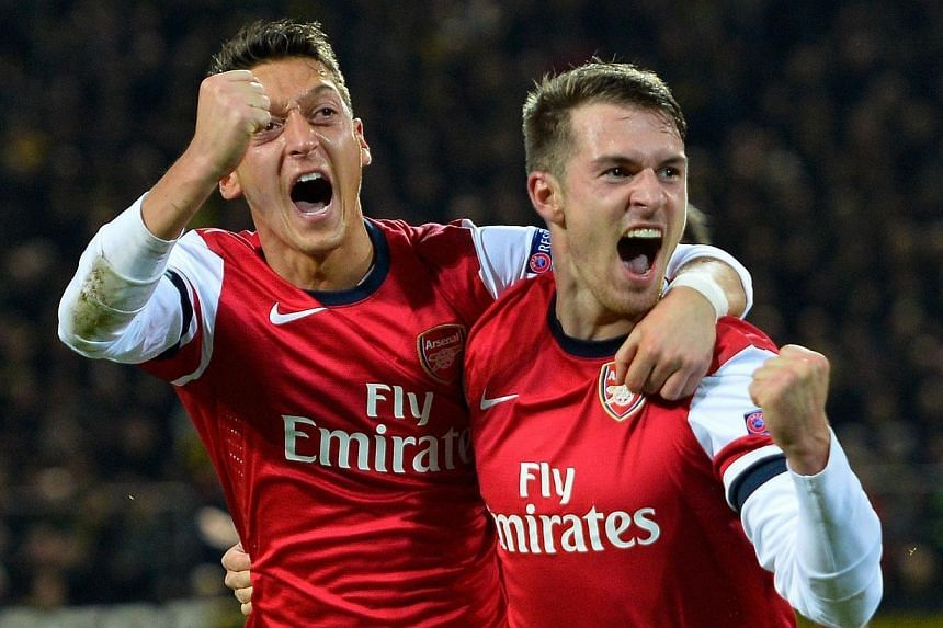 Arsenal midfielder Aaron Ramsey (right) celebrates scoring the opening goal with teammate Mesut Oezil during their Uefa Champions League group F match against Borussia Dortmund in Dortmund on Thursday, Nov 7, 2013. Ramsey's headed goal in the 62nd mi