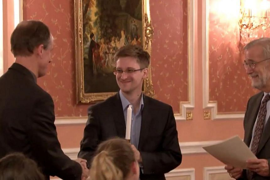 In this image made from video released by WikiLeaks on Friday, Oct 11, 2013, former National Security Agency systems analyst Edward Snowden, center, receives the Sam Adams Award in Moscow, Russia. -- FILE PHOTO: AP