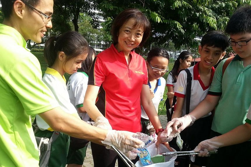 Guest of honour Er. Dr Lee Bee Wah (in red) picking up trash with students from Huamin Primary School as part of Waterways Clean-up @ North West, a programme to instill greater environmental awareness in youth. Some 175 pupils helped kick off a new e