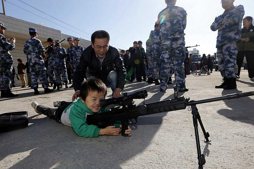 A boy plays with an unloaded gun during a Special Weapons and Tactics (SWAT) open day in Qingdao, Shandong province, Nov 7, 2013. -- PHOTO: REUTERS