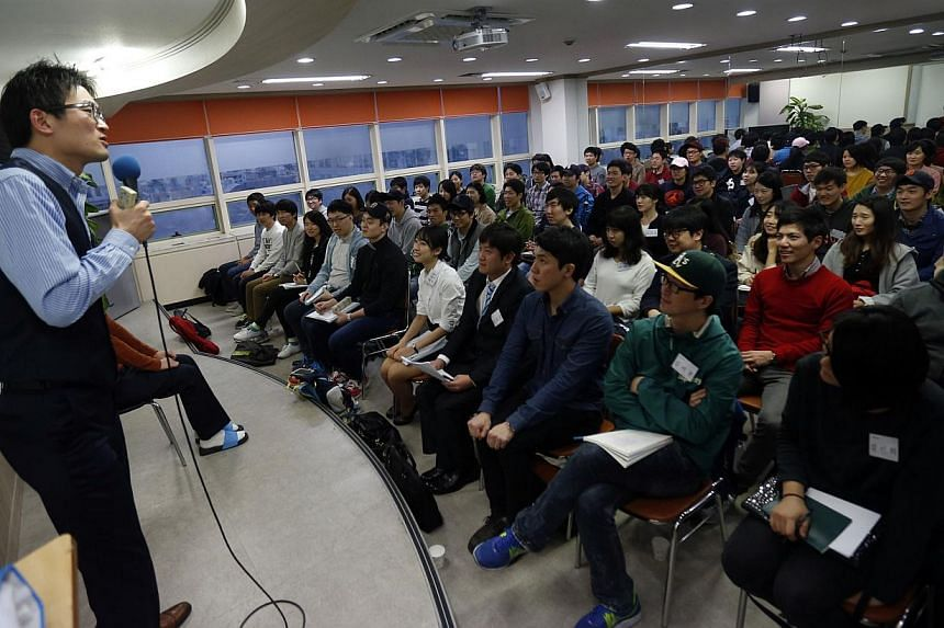 "Mr Im Chan Soo (left) gives a lecture on Samsung job interviews at his private cram school in Busan, about 420 km southeast of Seoul on Oct 28, 2013. In the cram school, 70 college students packed into a classroom, chanting ""We can do it!"" as they st"
