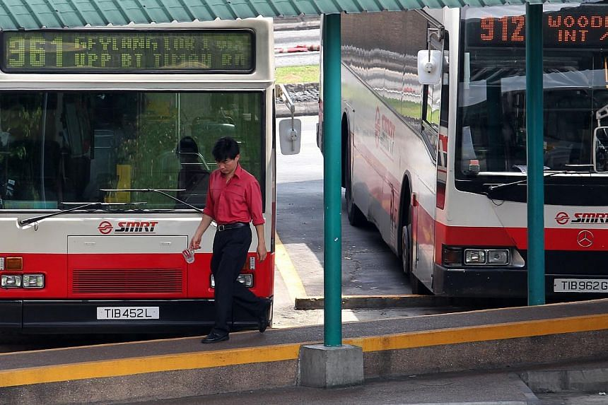 An SMRT bus driver leaves the bus to take a break at the Woodlands bus interchange. A new wage model will allow an average local bus driver working at SMRT to earn as much as $1,000 more, or $3,500 a month. -- FILE PHOTO: SEAH KWANG PENG