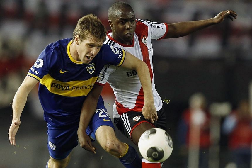 Boca Juniors' Claudio Riano (left) is challenged by River Plate's Eder Alvarez Balanta during their Argentine Championship First Division soccer match in Buenos Aires on Oct 6, 2013.Outstanding River Plate defender Eder Alvarez Balanta is one o