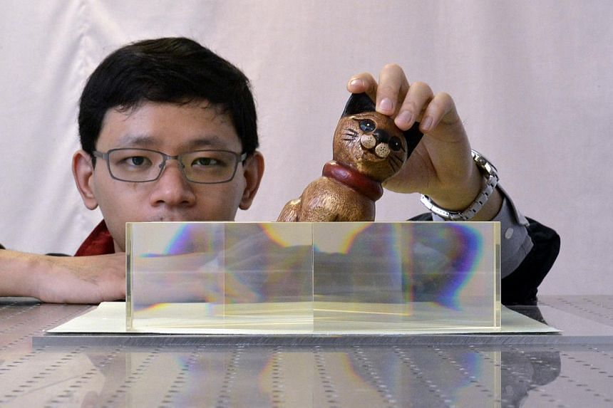 NTU School of Physical and Mathematical Science researcher Zhang Baile showing how his team's ''invisibility cloak'' works. The research is believed to be the first of its kind in this area. -- ST PHOTO: DESMOND FOO