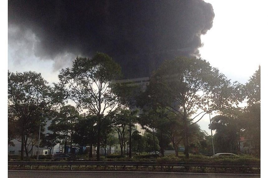 A fire broke out at an industrial building in Tuas on Friday evening. Pictures provided by Straits Times readers in the vicinity showed thick plumes of black smoke from the building.-- PHOTO: TWITTER OF LARRY TAN
