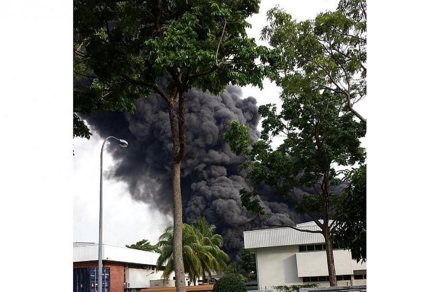 A fire broke out at an industrial building in Tuas on Friday evening. Pictures provided by Straits Times readers in the vicinity showed thick plumes of black smoke from the building.-- PHOTO: TWITTER OF @BG_yoshi
