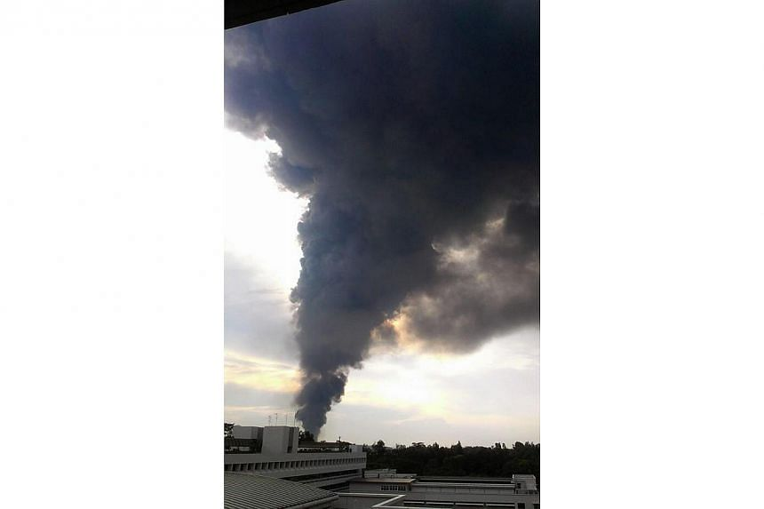 A fire broke out at an industrial building in Tuas on Friday evening. Pictures provided by Straits Times readers in the vicinity showed thick plumes of black smoke from the building.-- PHOTO: TWITTER OF AVIMANYU KISHWAR