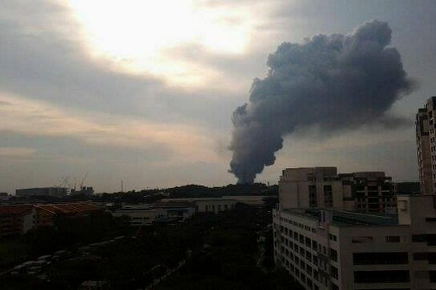 A fire broke out at an industrial building in Tuas on Friday evening. Pictures provided by Straits Times readers in the vicinity showed thick plumes of black smoke from the building.-- PHOTO: NORA SHAISTA