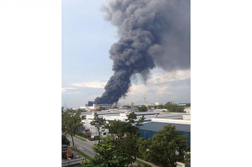A fire broke out at an industrial building in Tuas on Friday evening. Pictures provided by Straits Times readers in the vicinity showed thick plumes of black smoke from the building.-- PHOTO: TWITTER OF @SCCHUA