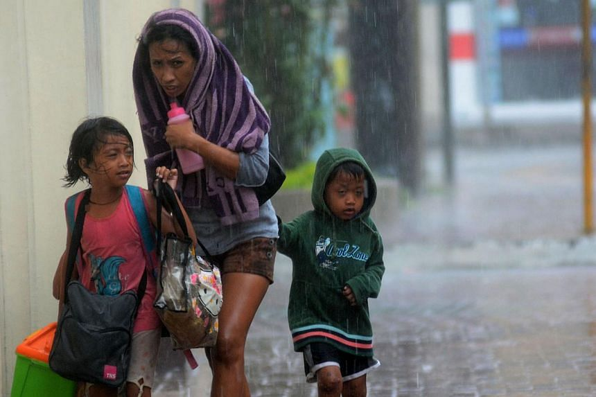 A mother and her children brave heavy rains as they head for an evacuation centre amidst strong winds as Typhoon Haiyan pounded Cebu City, in central Philippines on Friday, Nov 8, 2013.Filipinos in Singapore are keeping vigil in the wake of eve