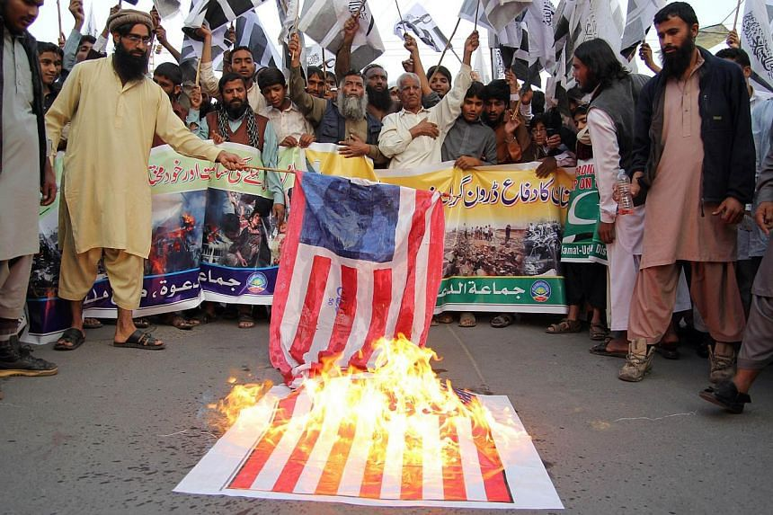 Supporters of banned Pakistan charity organisation Jamaat-ud-Dawa (JuD) torching the US flag during a protest against US drone attacks in the Pakistani tribal region, in Multan on November 8, 2013. Activists from right-wing religious parties staged p
