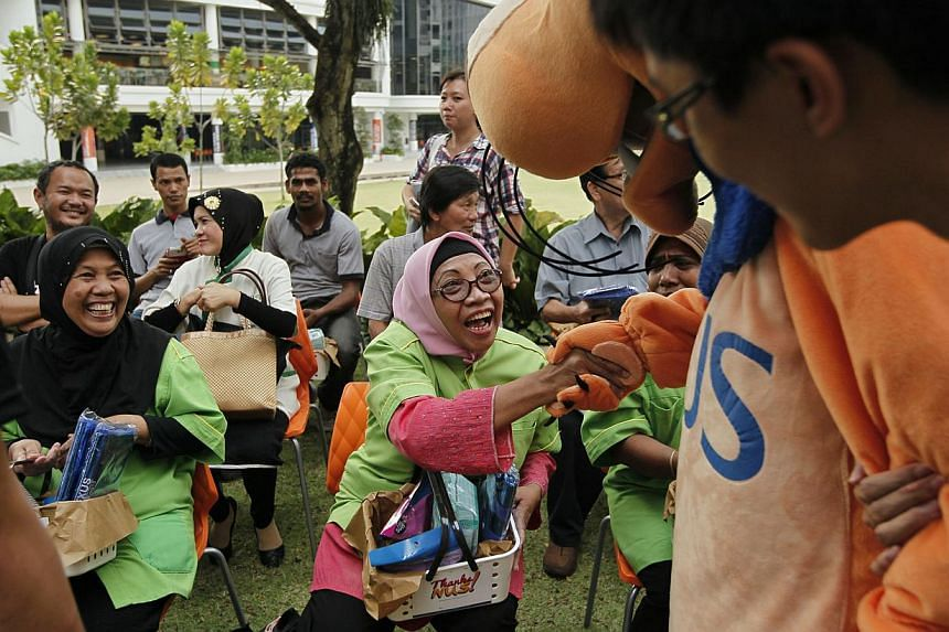 Saharah, a 63-year-old cleaner at National University of Singapore (NUS), clutches a picnic basket as reaches out to shake hands with the NUS mascot during the first ever appreciation event for support staff organised by the NUS Students Union (NUSSU