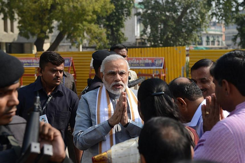 Chief Minister of the western Indian state of Gujarat and Bharatiya Janta Party (BJP) prime ministerial candidate Narendra Modi gestures as he greets supporters upon his arrival at The Bhadrakali Mandir in Ahmedabad on November 4, 2013, on the fourth