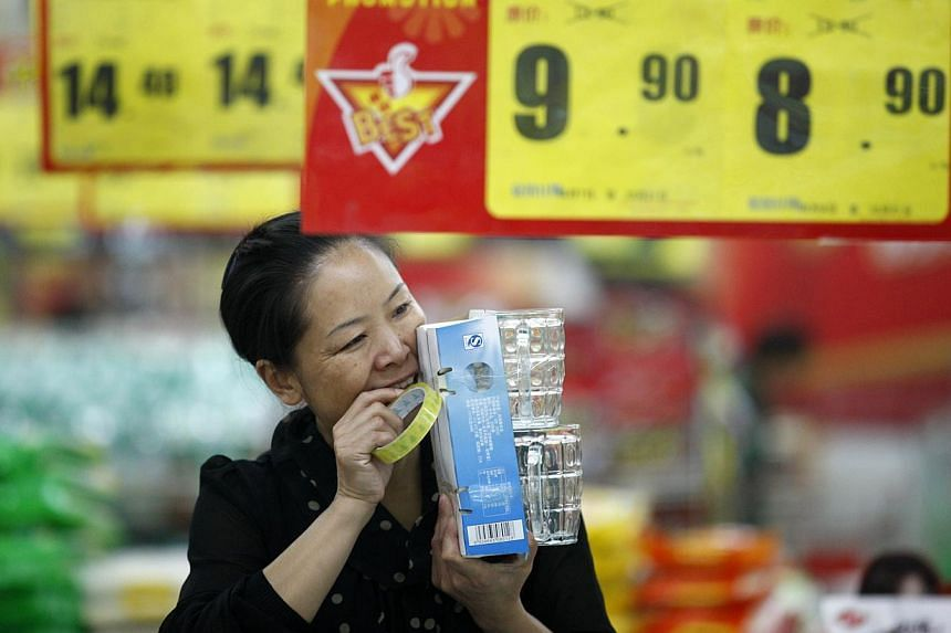 A sales girl packs goods in a supermarket in Huaibei, central China's Anhui province.China's annual consumer inflation climbed to an eight-month high of 3.2 per cent last month, driven by food prices, adding to market worries about policy tight