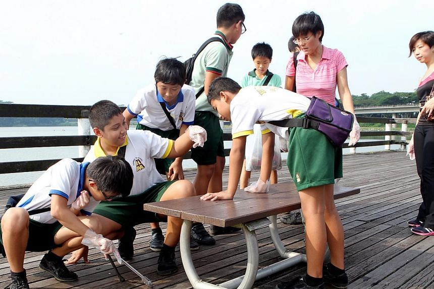 Huamin Primary School teachers Teo Siew Hong (second from right), 46, and Ng Poh Lin (right), 37, picking up litter with the school's pupils along the banks of Lower Seletar Reservoir, as part of the Waterways Clean-up @ North West programme yesterda