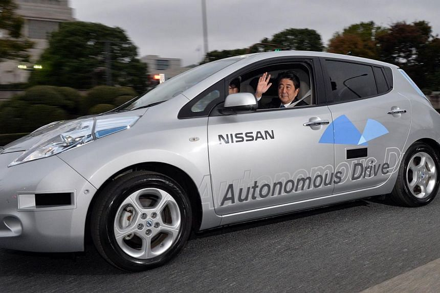 Japanese Prime Minister Shinzo Abe (centre) waves during a test drive of Nissan Motor's autonomous vehicle in Tokyo on Saturday, Nov 9, 2013. MrAbe took a ride in several self-driving vehicles on the public roads in the capital on Saturday, sho