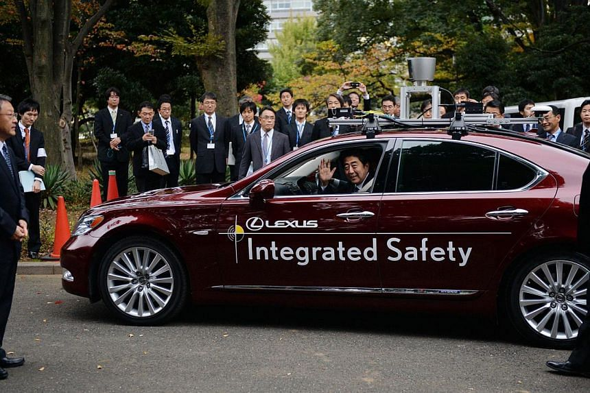 Japanese Prime Minister Shinzo Abe (centre) waves during a test drive of Toyota Motor's autonomous vehicle in Tokyo on Saturday, Nov 9, 2013. -- PHOTO: AFP