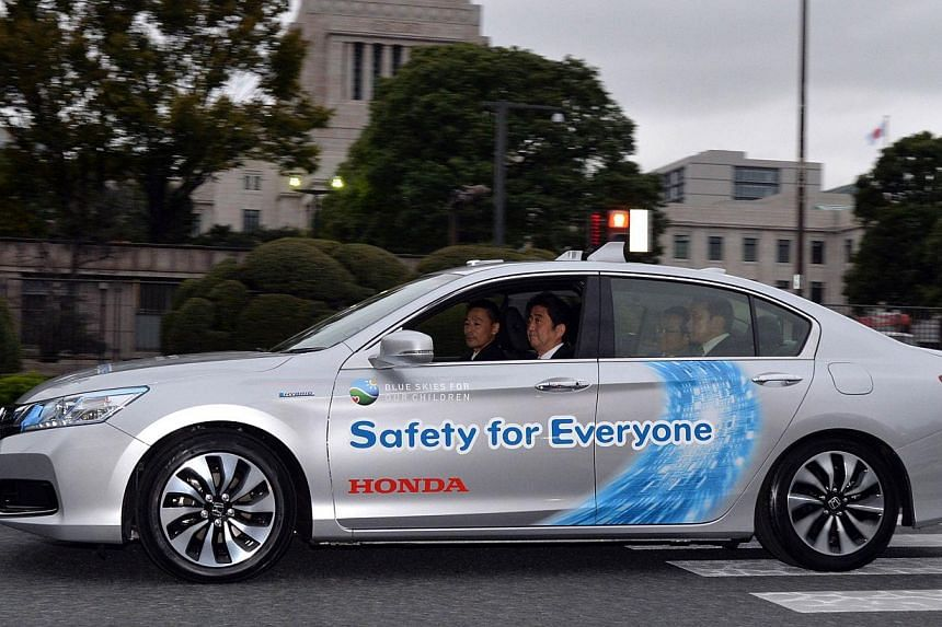 Japanese Prime Minister Shinzo Abe (centre) takes part in a test drive of Nissan Motor's autonomous vehicle in Tokyo on Saturday, Nov 9, 2013. -- PHOTO: AFP