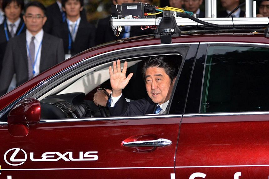 Japanese Prime Minister Shinzo Abe waves during a test drive of Toyota Motor's autonomous vehicle in Tokyo on Saturday, Nov 9, 2013. -- PHOTO: AFP