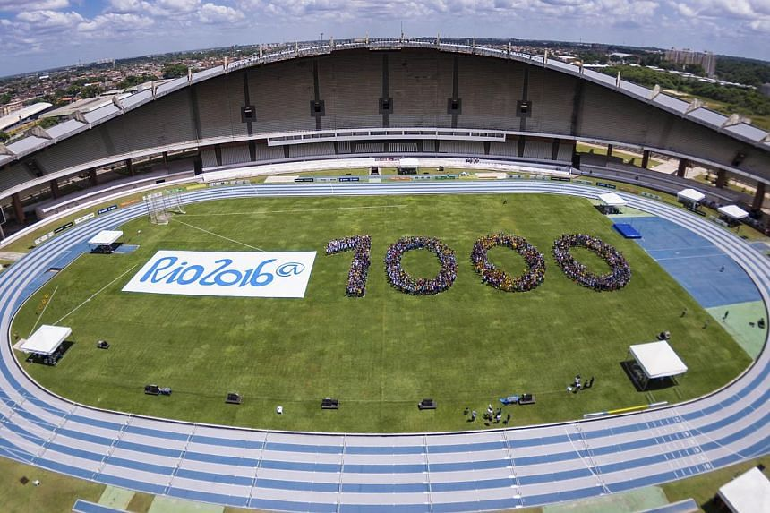 In this photo released by Rio 2016 Organizing Committee for the Olympic and Paralympic Games, youths form the number 1,000 to mark the number of days before the start of the Rio 2016 Olympic Games inside Mangueirao stadium in Belem, Brazil, on Friday