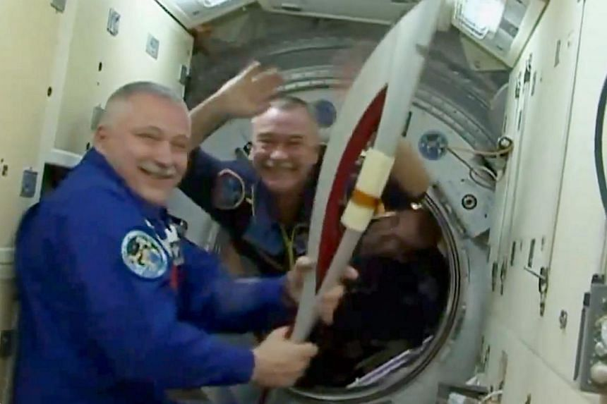 Expedition 37 commander Fyodor Yurchikhin (L) holds the Olympic torch that will be used to light the Olympic flame for the 2014 Winter Games in Sochi, Russia after Expedition 38 cosmonaut Mikhail Tyurin handed it over aboard the International Space S